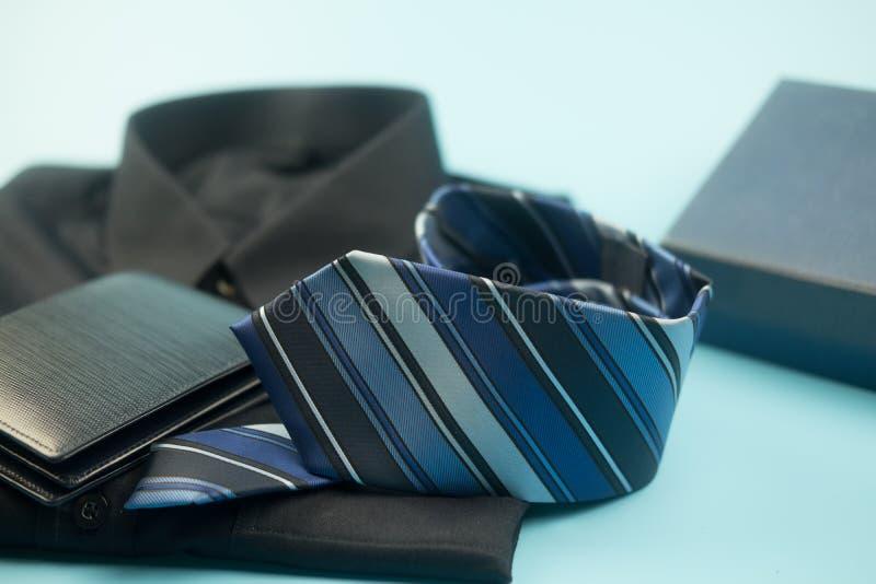 Rayure bleue de cravate et portefeuille bleu sur le fond bleu images stock
