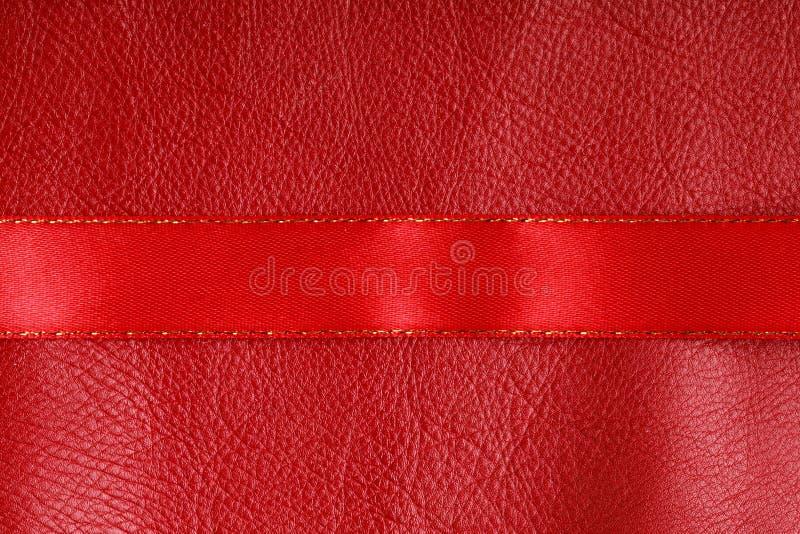 Rayure rouge brillante de ruban sur le fond en cuir. image stock