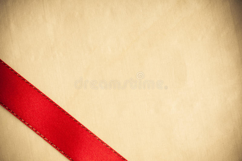 Rayure rouge de ruban sur le fond lumineux de tissu. photos stock