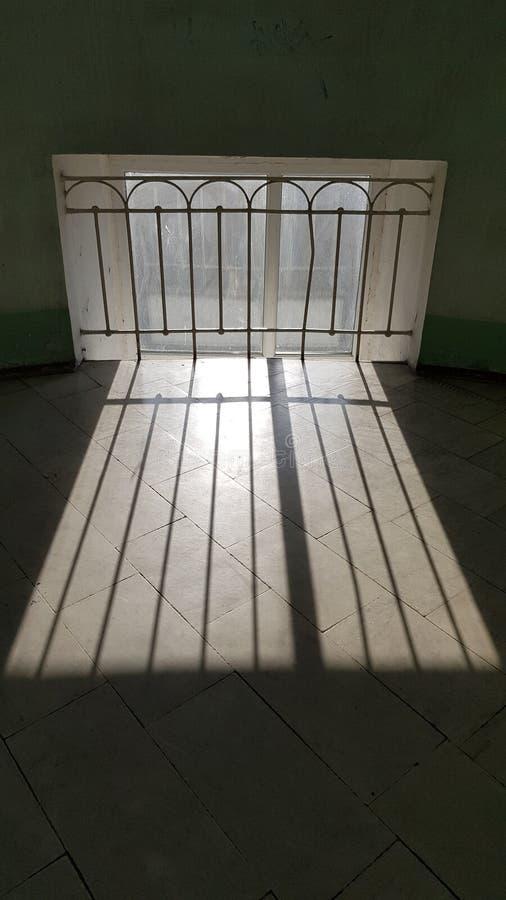Rayures de Sunbeam sur le plancher de tuiles en pierre près de la rétro grille de fenêtre de style photographie stock