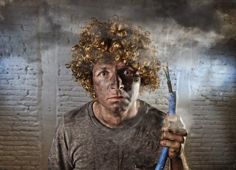 Razący prądem mężczyzna z kablowym dymieniem po domowego wypadku z brudnym burnt twarz szokiem raził prądem wyrażenie zdjęcie royalty free