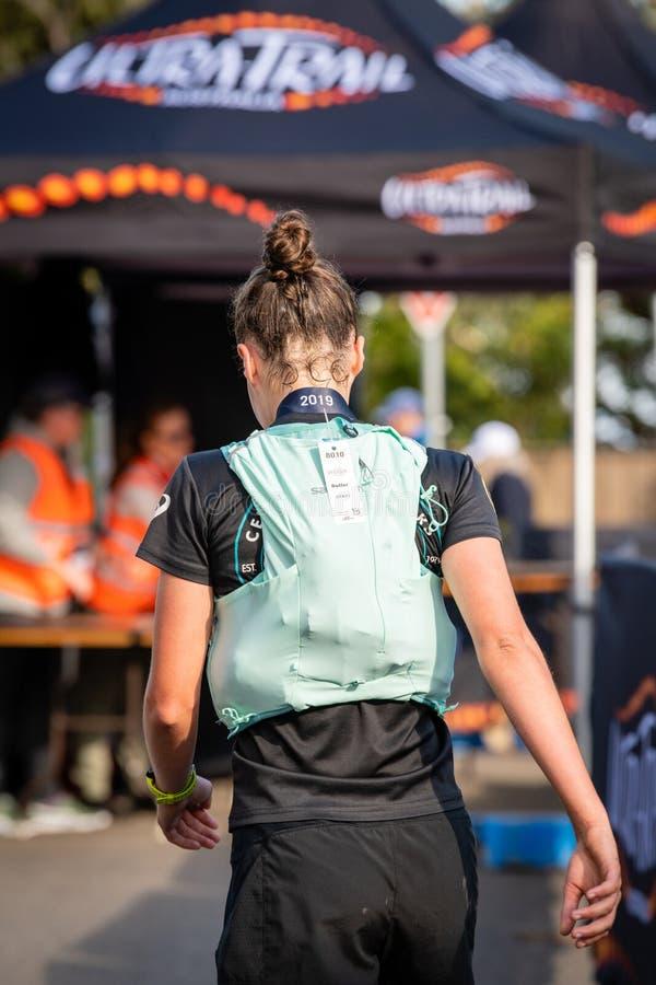 Raza de Australia UTA11 del Ultra-rastro El corredor Sophie Butler en la meta, se distrae para medir el tiempo de encargados imagen de archivo