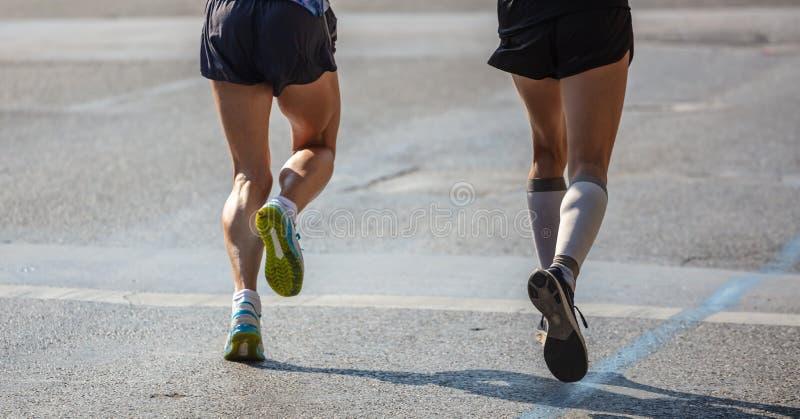 Raza de funcionamiento del maratón, dos corredores en los caminos de ciudad, detalle en las piernas fotos de archivo