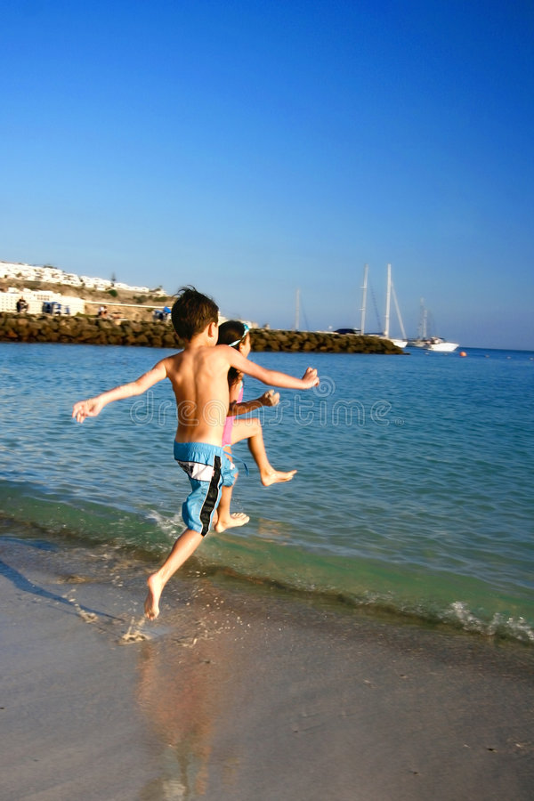Raza de la diversión de los niños a la playa imagen de archivo