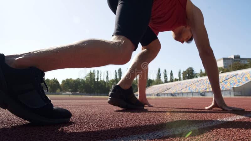 Raza del principio del deportista con el comienzo bajo, entrenamientos profesionales para la victoria fotografía de archivo
