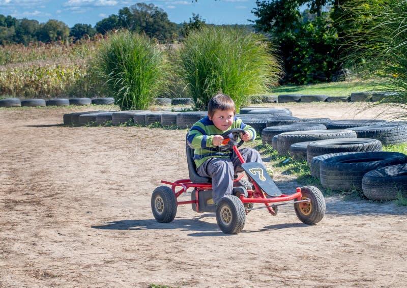 Razas felices del muchacho alrededor de una pista de tierra fotos de archivo