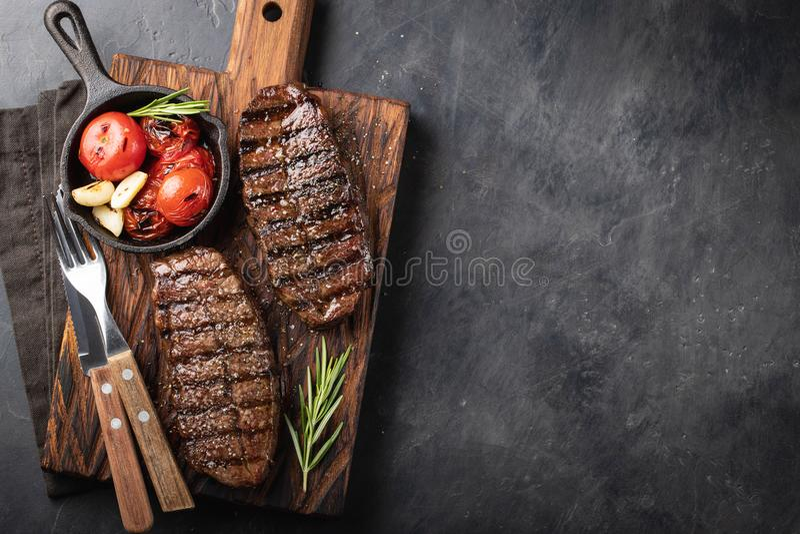 Razas preparadas de la carne de vaca de la cuchilla del top del filete del primer de Angus negro con el tomate de la parrilla, aj fotografía de archivo libre de regalías