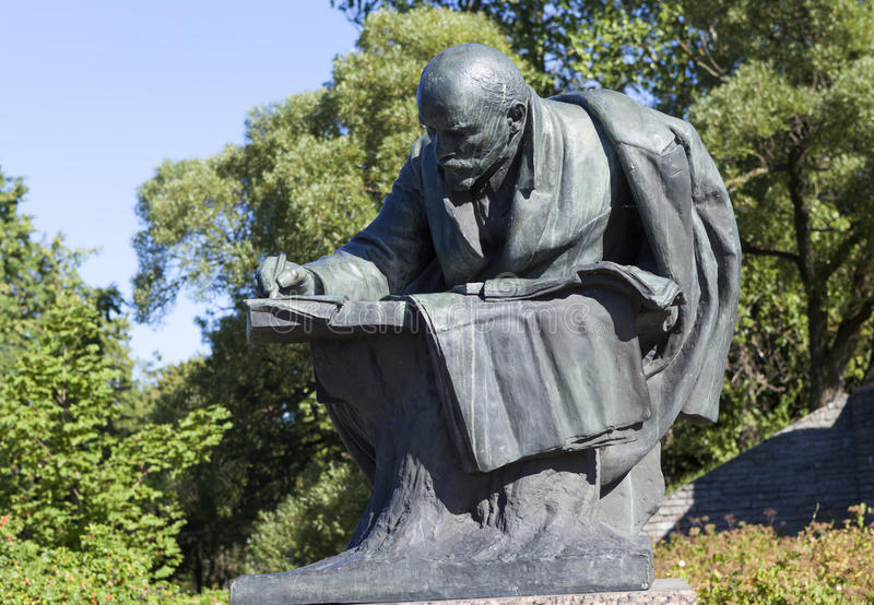 RAZLIV, RUSSIA - AUGUST 15, 2015: Photo of Lenin Monument. Sculpture muzhschiny, bent over a book on the background of sculptural letters Lenin, Primorsky stock image