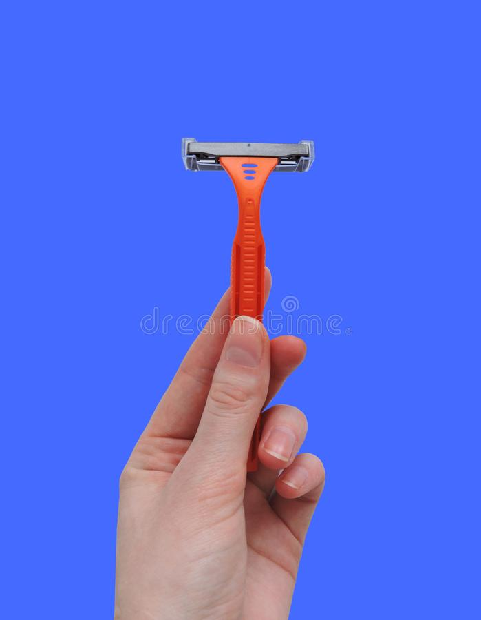 Razor in a female hand on a white background. Removal of unwanted hair. top view. Concept of using razor. Orange men`s razors. Removal of unwanted hair. top view stock photography