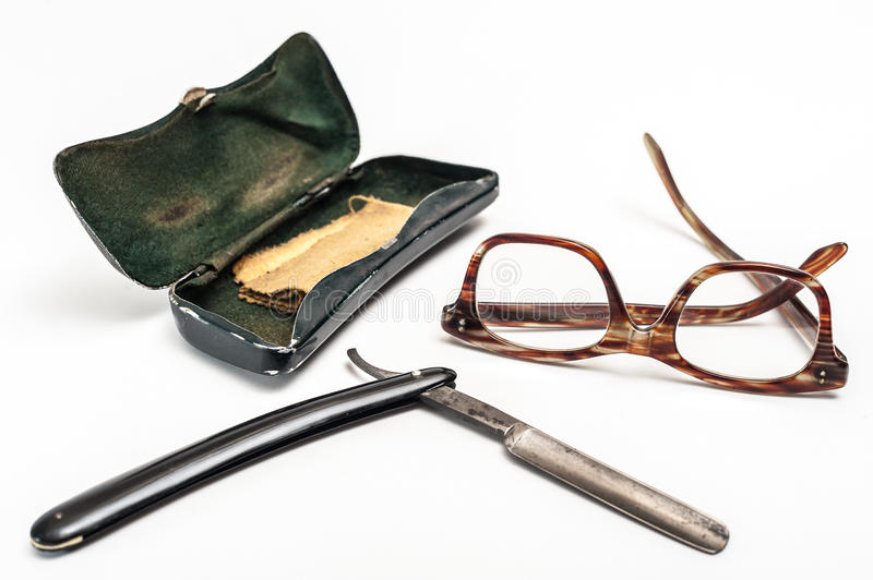 Razor and glasses. Old and worn rusty razor, glasses and glasses case on a white background royalty free stock image