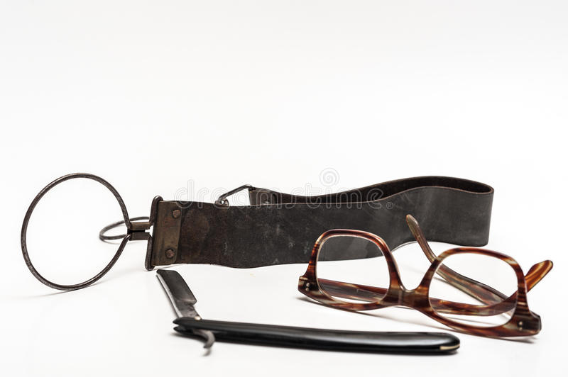 Razor and glasses. Old and worn rusty razor, sharpening leather, glasses on a white background royalty free stock images