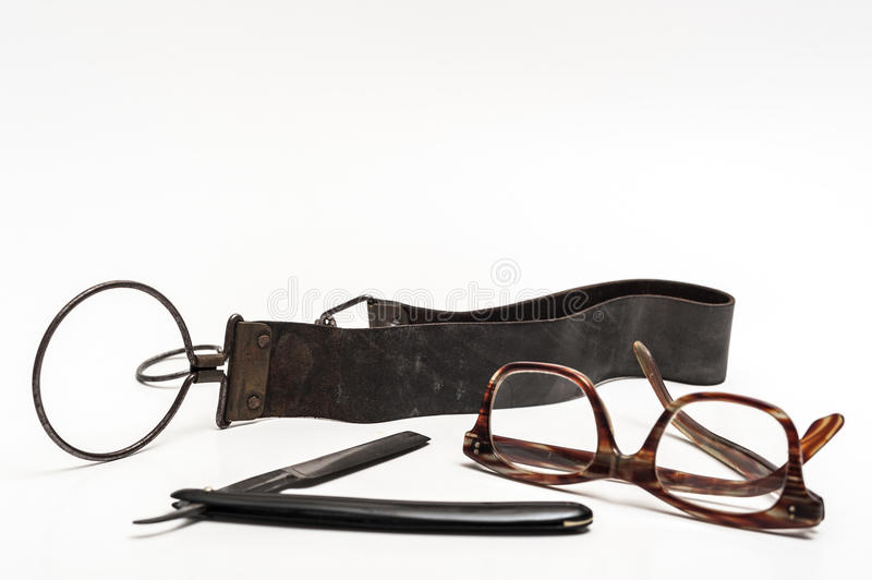 Razor and glasses. Old and worn rusty razor, sharpening leather, glasses on a white background stock photos