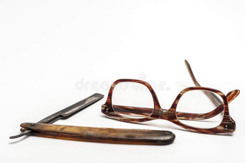 Razor and glasses. Old and worn rusty razor, glasses on a white background stock photography