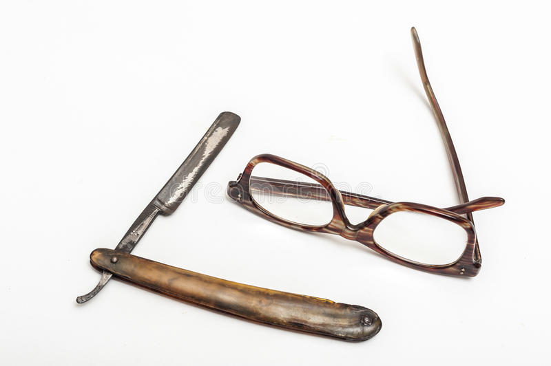 Razor and glasses. Old and worn rusty razor, glasses on a white background stock images