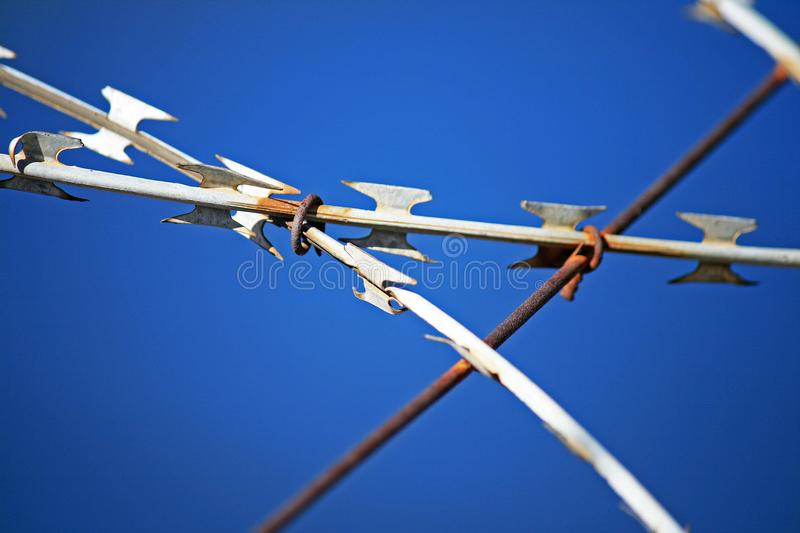 RAZOR WIRE AGAINST THE BLUE SKY stock photo