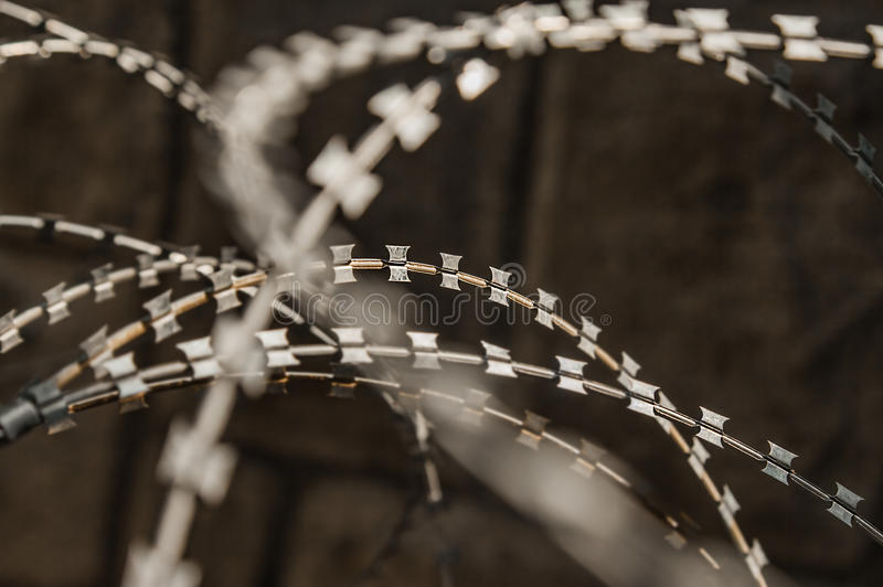 Razor wire fence. Close-up of a rusty metal razor fence wire outdoors stock images