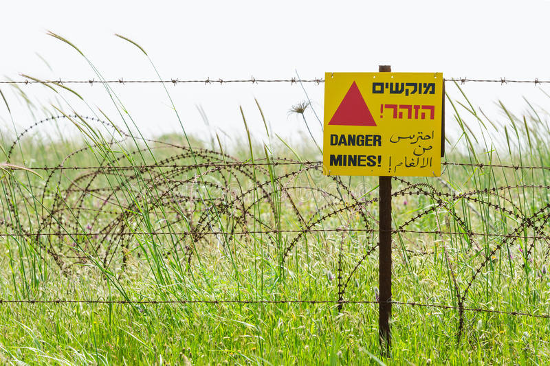 Razor wire guard fence and warning sign on mines field royalty free stock images