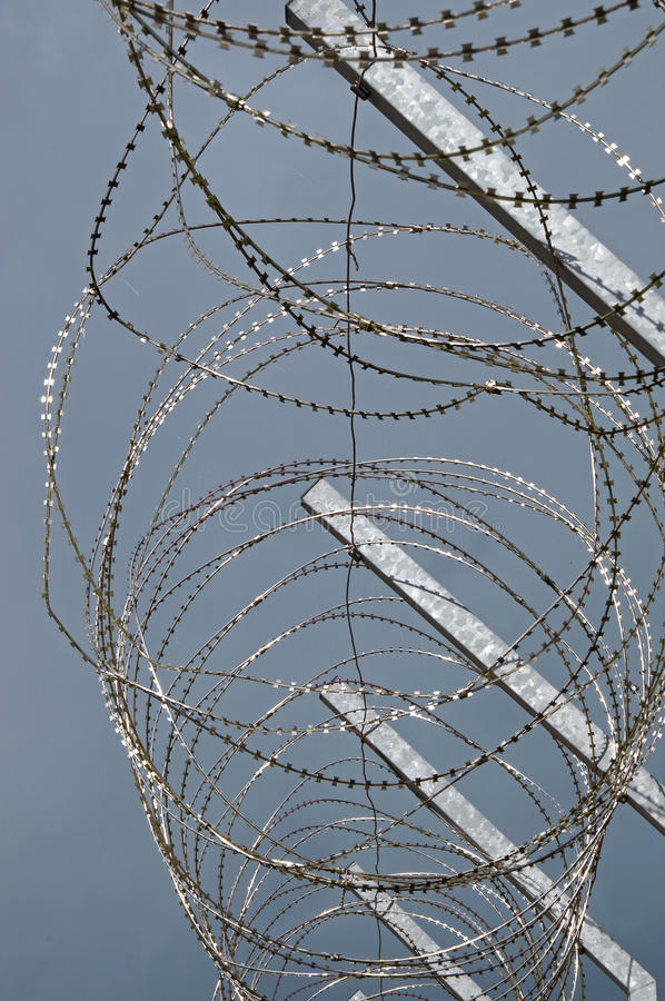 Razor wire on prison fence royalty free stock images