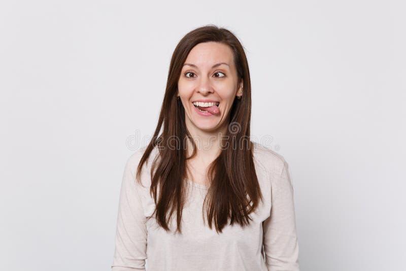 Razy grappige jonge vrouw Ð ¡ met afgeschuinde ogen in lichte kleren die tong tonen, die rond geïsoleerd op witte muurachtergrond royalty-vrije stock foto