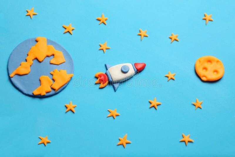 Razzo creativo del plasticine del mestiere nello spazio aperto, sogni dell'astronauta Stelle, pianeta Terra e luna Arte del fumet fotografia stock libera da diritti