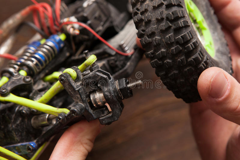 Rc car model toy wheel repair. Rc radio control car crawler model whell repair on wooden background. Green toy suv in repairshop workplace, free space stock photos