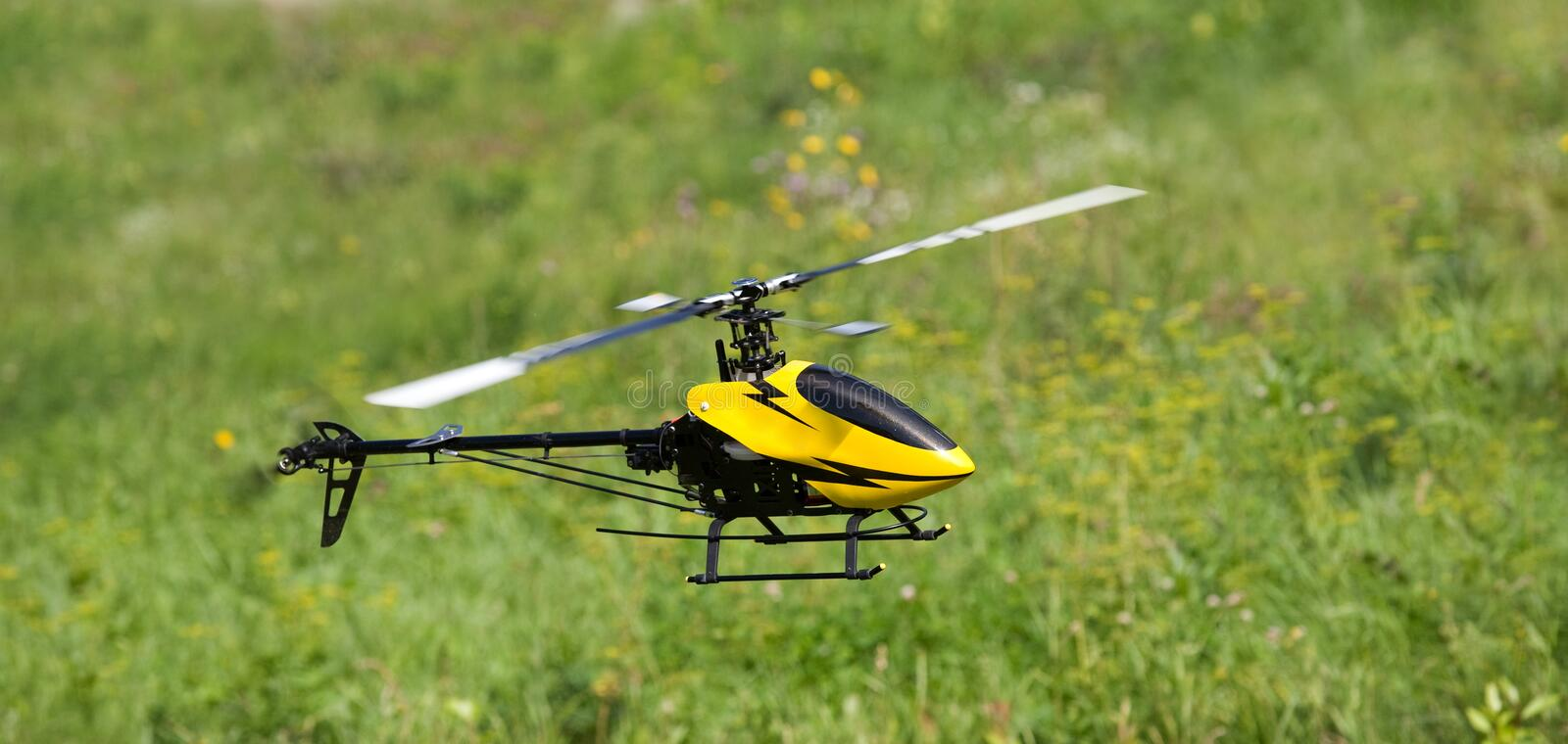 Rc helicopter. Rc controlled helicopter hovering above grass royalty free stock photography