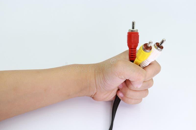 3 RCA Jack Plug Adapter Audio en la mano del niño aislada en el fondo blanco fotos de archivo libres de regalías