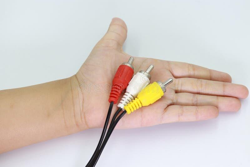 3 RCA Jack Plug Adapter Audio na mão da criança isolada no fundo branco imagens de stock