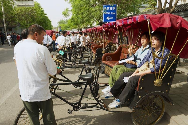 Rckshaw transporta a pasajeros en la calle de Futong al lado del lago Houhai en Pekín, China imagen de archivo libre de regalías