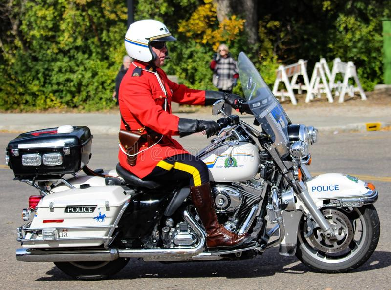 RCMP Motorcycle rider in red surge uniform. Police two-wheeled motorcycle Mounties colorful uniformed riding Canadian Royal red patrol riding royalty free stock images