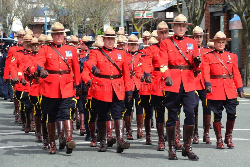 RCMP officers march in unison. Victoria BC,Canada,April 19th 2018.RCMP police officers in their red tunics march to the church for a funeral for a fallen officer royalty free stock image