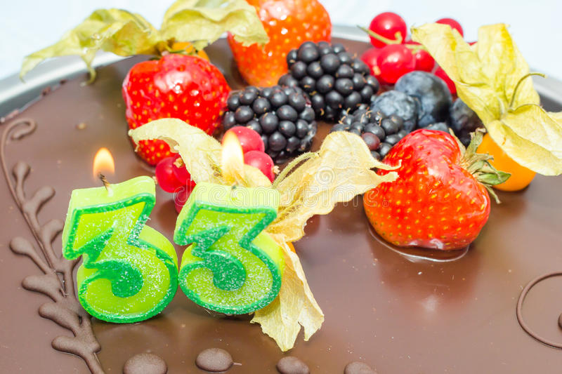 33rd birthday candles. On a chocolate mallow cake royalty free stock image