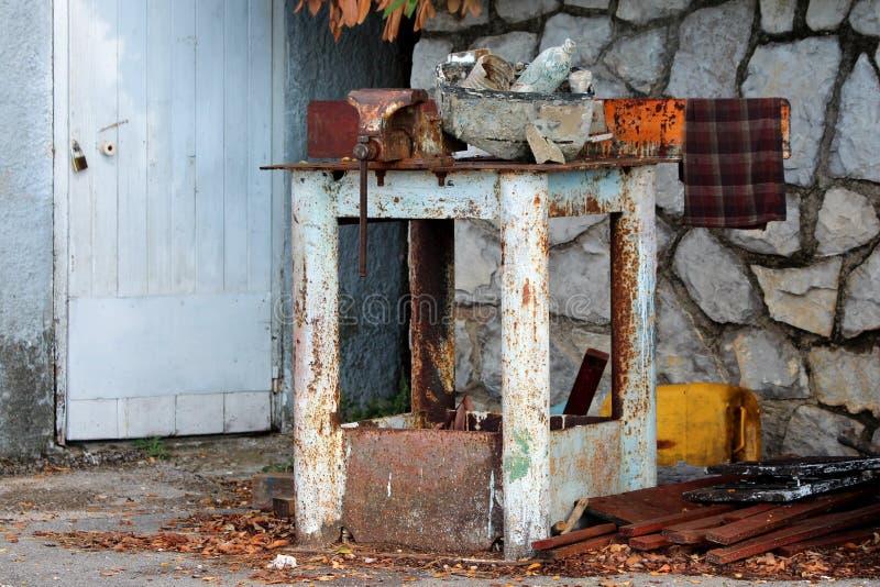 Rdzewiejąca workbench rozpusta wspinająca się na starym metalu stole otaczającym z materiałem budowlanym i śmieci na kamiennej śc obrazy stock