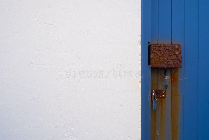 Rdzewiejący drzwiowy kędziorek na błękitnym drzwi obraz royalty free