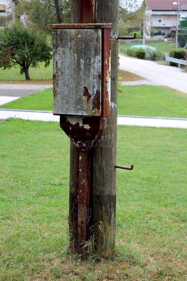 Rdzewiejący metalu telefoniczny pudełko z metalu drutu budynek mieszkalny wspinał się na starym drewnianym oszczędnościowym słupi fotografia stock