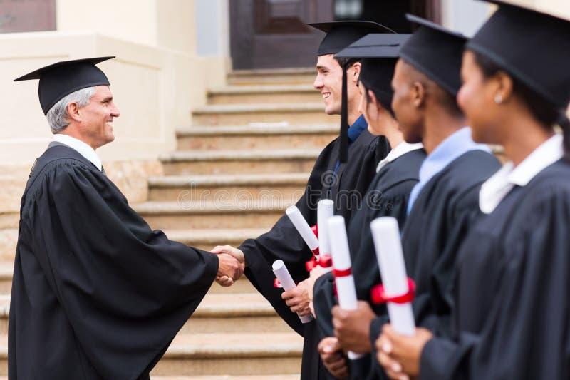 Reçoit un diplôme le doyen de poignée de main photographie stock libre de droits