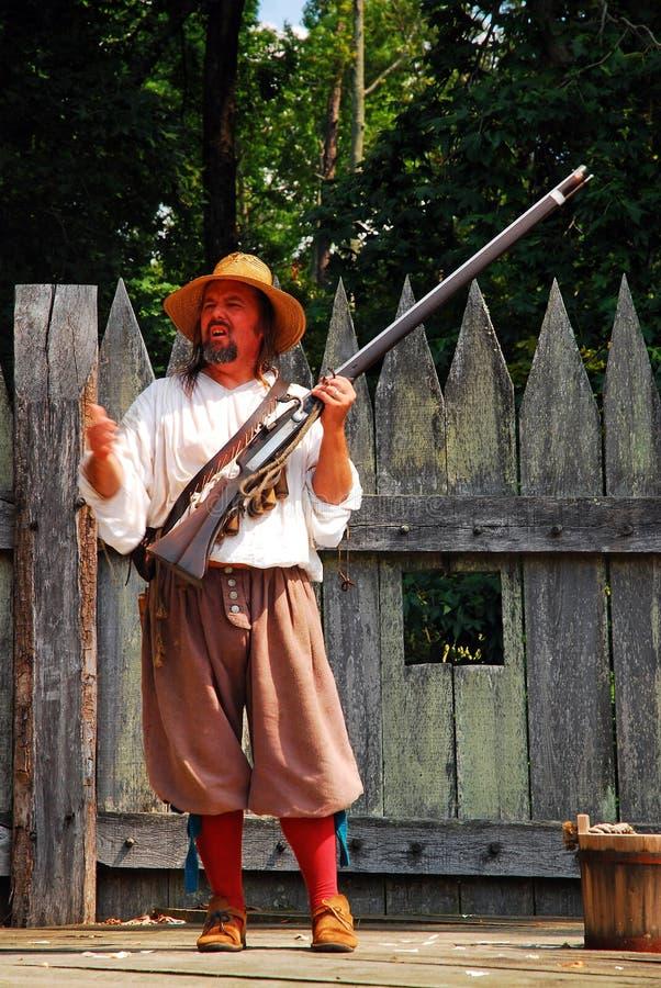A re-enactor demonstrates a colonial era rifle. A costumed re-enactor demonstrates a colonial era gun in Jamestown, Virginia royalty free stock photo