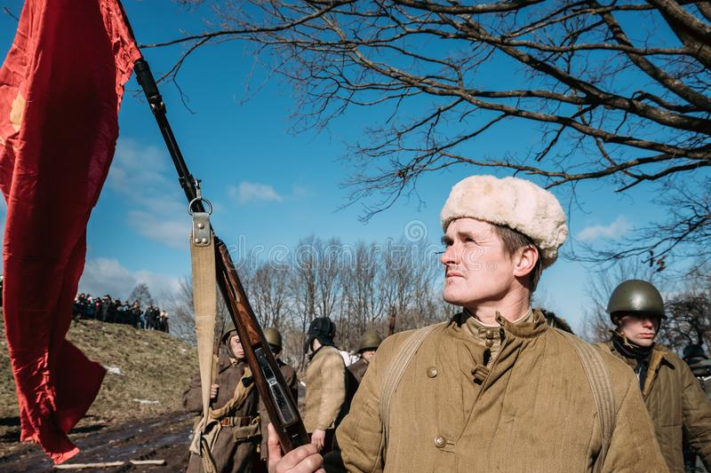 Re-enactor Dressed As Russian Soviet Infantry Soldier Of World War II Holding Red Flag. Rogachev, Belarus - February 25, 2017: Re-enactor Dressed As Russian royalty free stock image