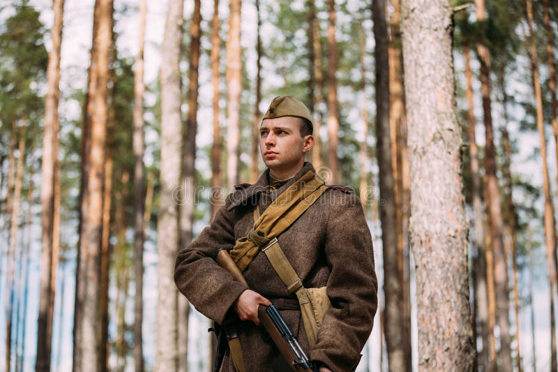 Re-enactor Dressed As Russian Soviet Infantry Soldier Of World War II With Rifle Weapon In Autumn Spring Forest. Pribor, Belarus - April 23, 2016: Re-enactor royalty free stock photos