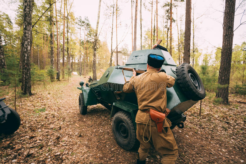 Re-enactor Dressed As Soviet Russian Red Army Infantry Soldier. Of World War II Shooting In Attack With Rifle Under Cover Of An Armored Car In Forest At Spring stock image