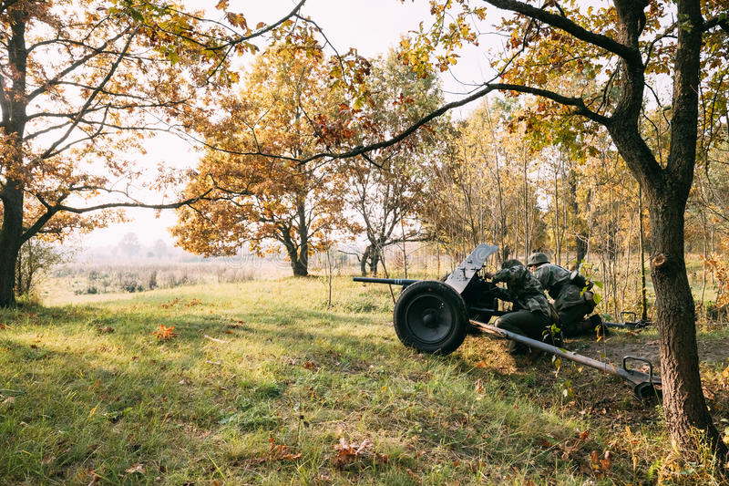 Re-enactors Dressed As German Wehrmacht Infantry Soldier In World War II. Hidden Sitting With German Anti-tank Gun Cannon Weapon In An Ambush In Trench In royalty free stock photos