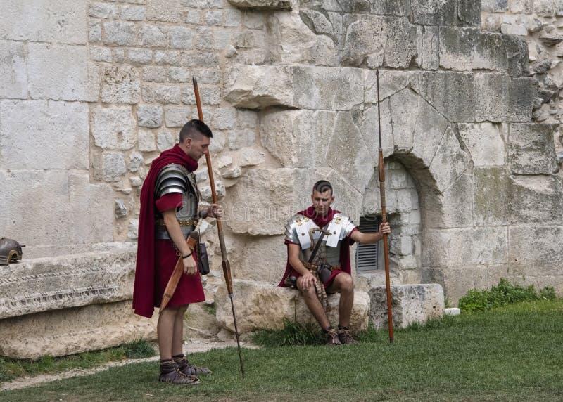 Re-Enactors kleedden zich aangezien Roman Legionnaires, om met Toeristen bij de poorten aan het Diocletian-Paleis wacht te stelle royalty-vrije stock foto's