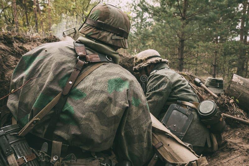 Re-enactors vestida como soldados de la infantería de Wehrmacht del alemán en la sentada ocultada Segunda Guerra Mundial foto de archivo