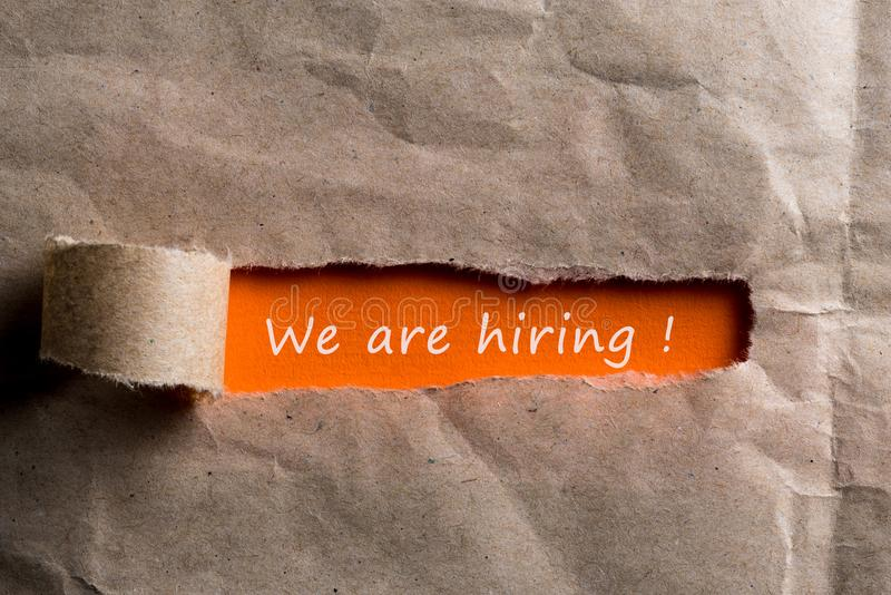 We`re Hiring, the phrase is written on orange paper in torn envelope, Human resource concept, strategy, plan, planning. stock image