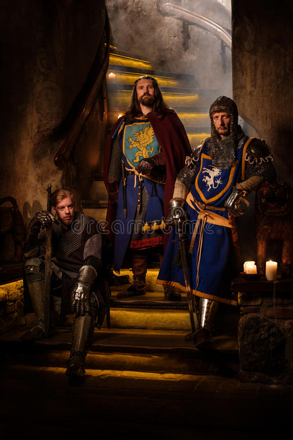 Re medievale con i suoi cavalieri nell'interno antico del castello immagine stock