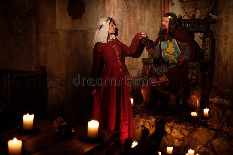 Re medievale con la sua regina nell'interno antico del castello fotografia stock