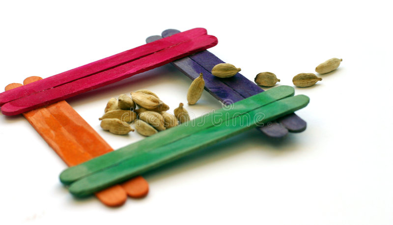 We're Moving!. Fun arrangement of cardamom pods and a colourful wooden frame made from painted ice popicle sticks. Concept photograph for moving to new house or royalty free stock photos