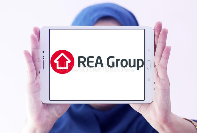 REA Group logo. Logo of REA Group on samsung tablet holded by arab muslim woman. REA Group is a global online real estate advertising company listed on the stock image