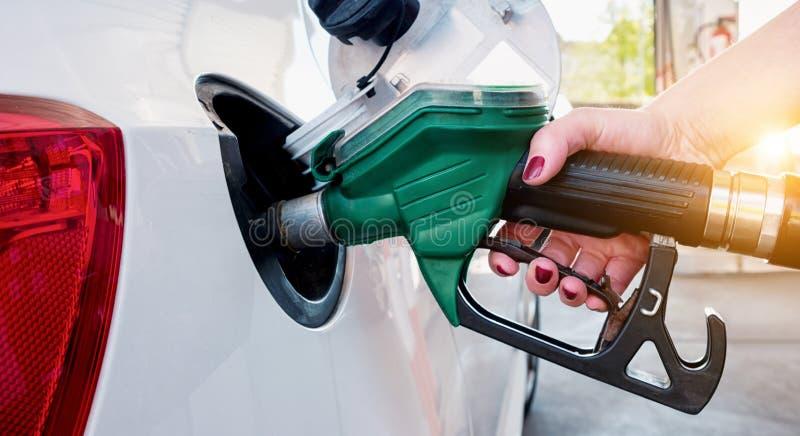 Reabastecimento do carro no posto de gasolina Óleo de bombeamento da gasolina da mulher fotografia de stock royalty free
