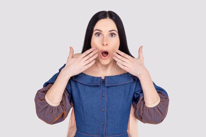 Reacciones humanas y concepto de las expresiones faciales La hembra europea joven morena preciosa con los ojos hizo estallar haci foto de archivo libre de regalías